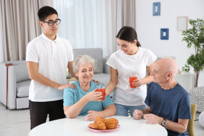 two caregivers preparing and assisting the old couple on their meal