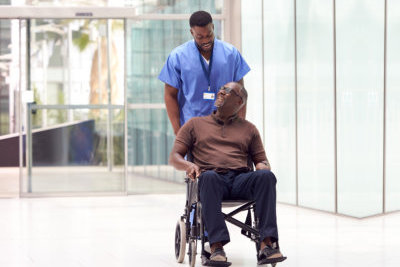 male healthcare escorting the old man