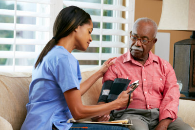 lady nurse checking the old man's blood pressure