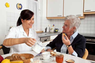 young caregiver preparing meal for the old woman