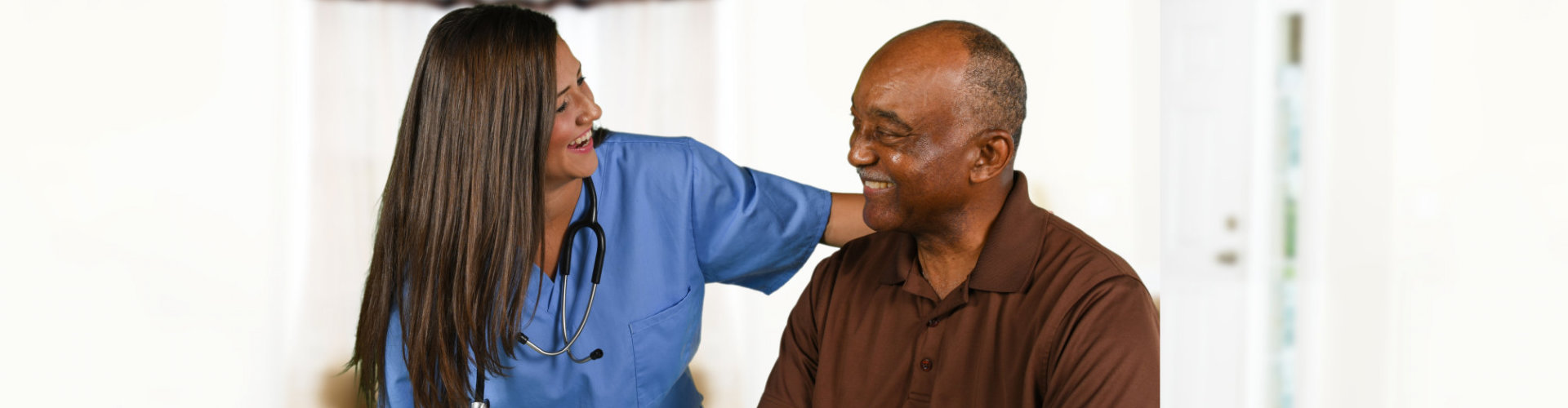 a lady healthcare and old man smiling